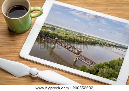 Historic railroad Katy Bridge over Missouri River at Boonville - reviewing aerial image on a digital tablet with a cup of coffee