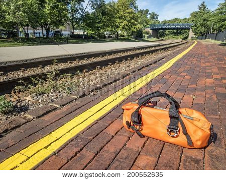Waiting for a train concept - a bright orange duffel on a station platform behind yellow line