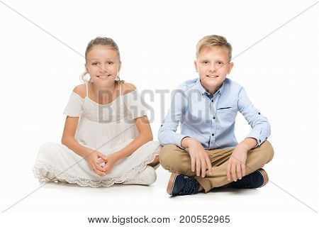 smiling preteen girl and boy looking at camera isolated on white