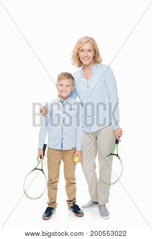 smiling woman and preteen boy holding tennis rackets and ball isolated on white