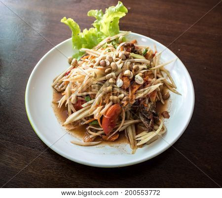 Papaya salad on wooden table (Som tum Thai). Look from top to bottom.