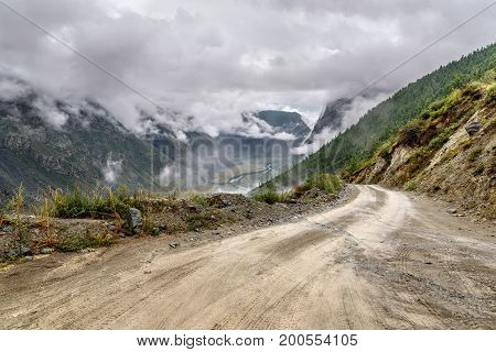 A picturesque view of the steep winding gravel mountain road through the pass part of a mountain serpentine passing the of the mountain in the rain and fog