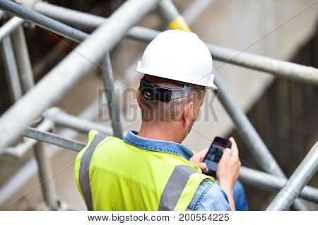 Workers inspecting construction works on a scaffold inside construction site