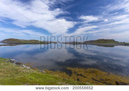 Fogo Island coastline with cloud reflections; Newfoundland, Canada