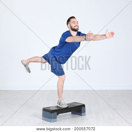 Young sporty man training legs with stepper in gym