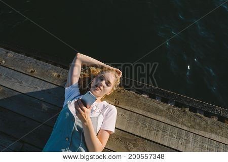 young beautiful blond girl teenager lying on pier the sea and listening to music. Young woman with earphones and phone outdoo
