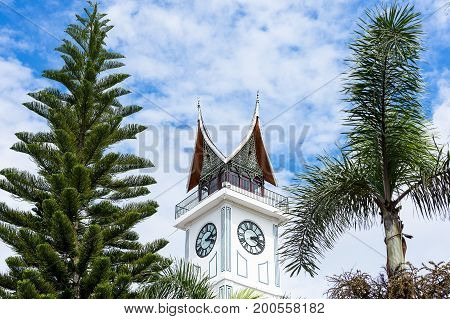 The Jam Gadang Big Clock Tower in Bukittinggi Sumatra Indonesia. A major landmark framed by tropical trees.