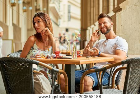 A beautiful young woman is upset to her handsome boyfriend because he is talking on the phone while they are having a coffee at a table on a terrace in Budapest, Hungary.