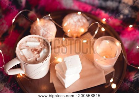Cup of coffee with sweets cake and candle stay on wooden tray in bed with christmas lights. Good morning. Selective focus.