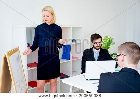 A businesswoman is presenting something at a meeting
