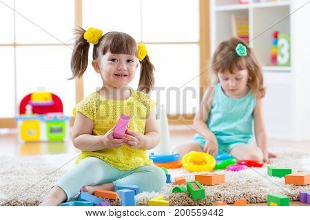 Children playing together. Toddler kid play with blocks. Educational toys for preschool and kindergarten child. Little girls build pyramid toys at home or daycare.