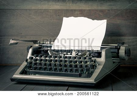 The old typewriter with a white ragged paper sheet is shot close-up on a board