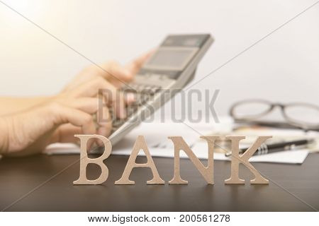 accountant with calculator and bank alphabet on desktop. concept business loan.