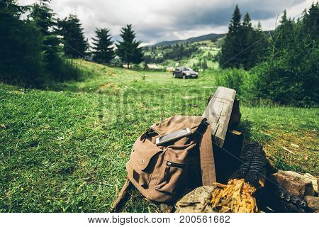backpack with mobile phone in forest with car on background in mountains
