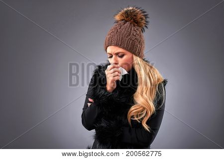 A beautiful young woman in an elegant black sweater and a brown hat feeling unwell and holding a tissue