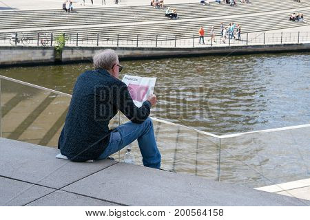 BERLIN, GERMANY - AUGUST 07, 2017: A man is sitting in the government quarter of Berlin on a staircase and reads the financial section of a newspaper.