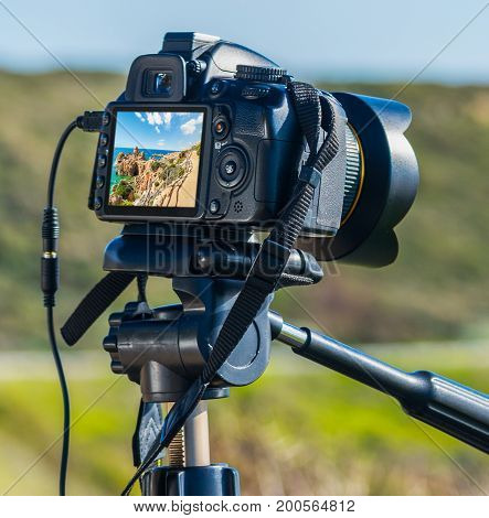 Dslr camera on tripod shooting Sardinian coast on a sunny day.