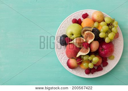 Top view on assortment of juicy fruits on white plate and turquoise wooden table background. Organic raspberries apricots apples figsplums grapes - summer dessert or snack. healthy eating concept