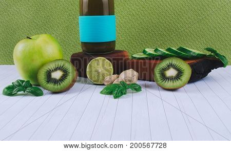 Detox diet concept: green smoothie with fruits and vegetables on white wooden table.