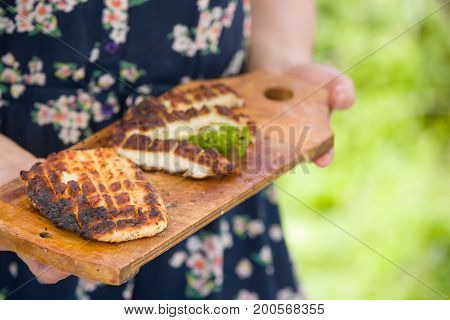 Top view on two grilled slices of homemade halloumi cheese on wooden borad in woman's hands. Outdoors..Grilling season. Healthy eating.