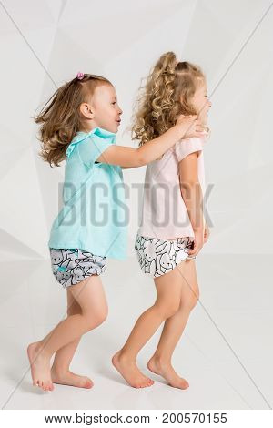 Two little funny and laughing girl in the identical clothes of different colors playing in white studio. Two girlfriends running after each other