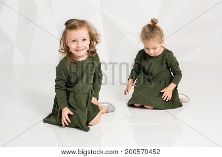 Two little girlfriends in the same dark green dresses sitting on the floor in a studio with white walls. Little girls posing on camera