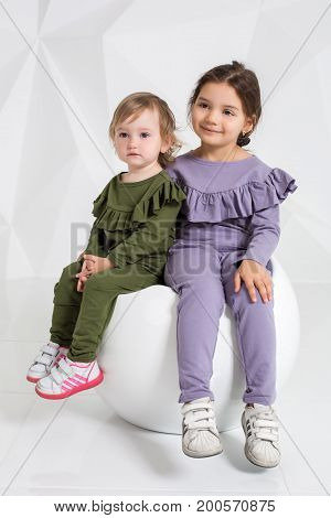 Children, two sisters 1.5 and 5 years old in the identical costumes of different colors, little girls on a white background in the studio sitting on a white chair.