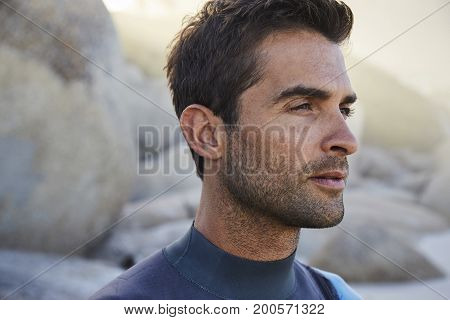 Good looking guy in wetsuit on beach looking away