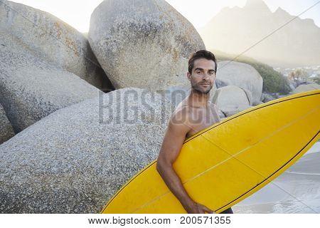Portrait of surfer dude holding board on rocky beach