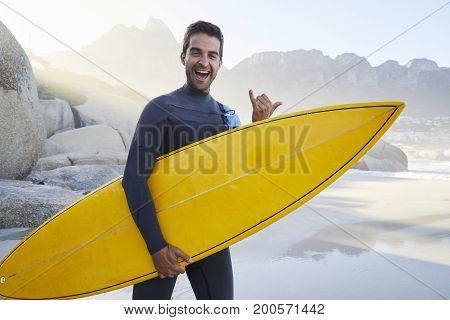 Gnarly surf dude gesturing to camera and holding board