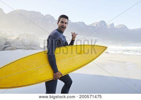Shaka sign surf dude holding board portrait