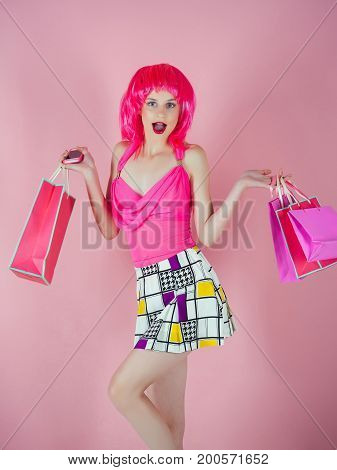 Woman with shopping bags. Girl wearing red wig and fashionable clothes. Fashion shopper with surprised face on pink background. Sale and black friday. Holidays celebration concept.