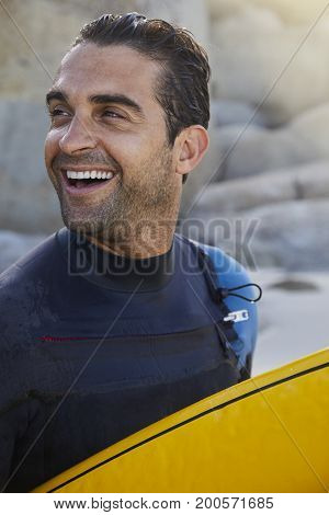 Laughing surf dude in wetsuit on beach looking away