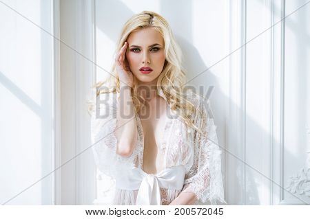 Fashionable female portrait of cute lady in white robe indoors. Close up beautiful sexy model girl in elegant pose. Closeup beauty blonde woman with hairstyle and makeup. Glamorous face with make up