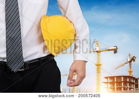Engineer holding a yellow helmet for the safety of workers with crane in the background