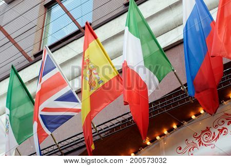 National flags of Italy Great Britain Spain Mexico and Russia on the wall of the building