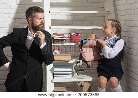 Man And Girl Near Bookshelf With School Supplies