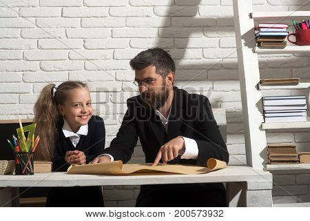 Teacher And Schoolgirl In Study Room On White Brick Background
