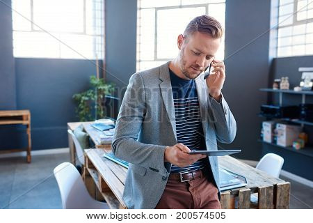 Focused young entrepreneur standing alone in a large modern office talking on a cellphone and working online with a digital tablet