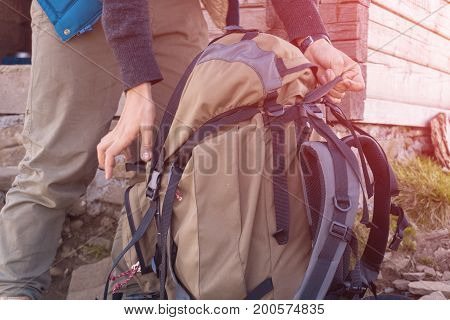 Man lifts travel backpack In the mountains. close-up.