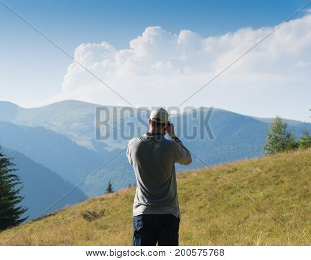 A man with a camera in the background of a mountain landscape.