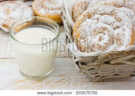 Traditional Spanish or Philippine pastry ensaimada. Powdered on cooling rack and in wicker basket. Glass of milk white wood table. Cozy rustic kitchen interior.