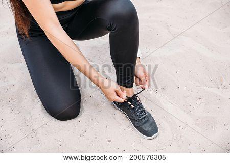 cropped view of sportswoman in sportswear tying shoelaces on sand