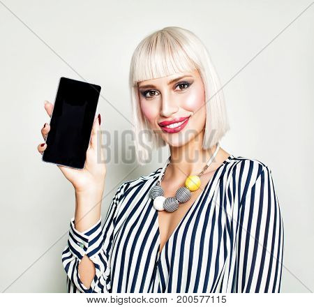 Smiling Woman Showing Empty Copy Space on Mobile Phone. Cell Phone Fashion Makeup Blonde Bob Hair