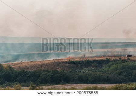 Burning grass in the fields and smoke from the fire rises, natural summer fires in the Rostov region, Russia