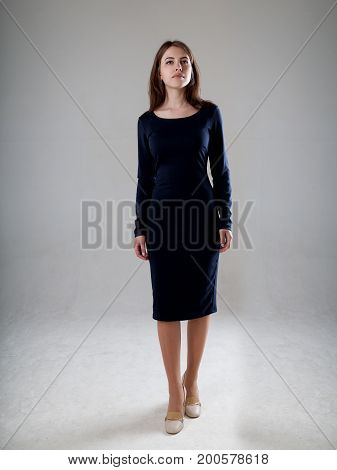 Beautiful Woman In A Black Dress Over Gray Background