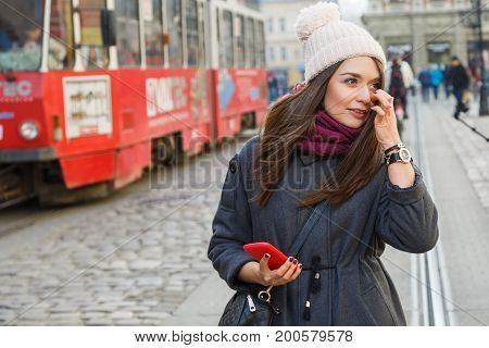 Attractive Young Woman Holding Smart Phone On The Street