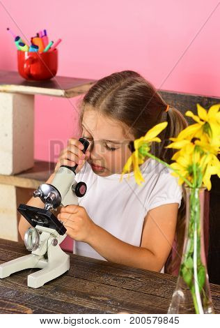 Girl With Concentrated Face Looks Into Microscope