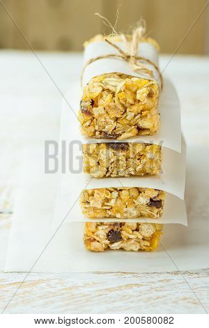 Homemade stacked muesli cereal bar with oats nuts raisins honey and dried apples. Lined with parchment paper tied with twine. White wood background. Healthy diet snack dessert.