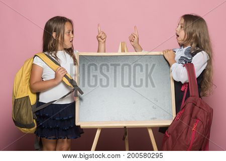Children with big schoolbags copy space. Girls in school uniform hold fingers up on pink background. Schoolgirls with smiling faces stand near blackboard. Education and school concept